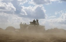Ukrainian army servicemen around an armoured vehicle are seen through dust raised by passing vehicles near Debaltseve